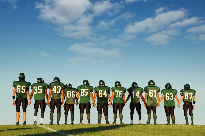 Football players holding hands against a blue sky