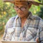 Old man with glasses and hat holding a tablet